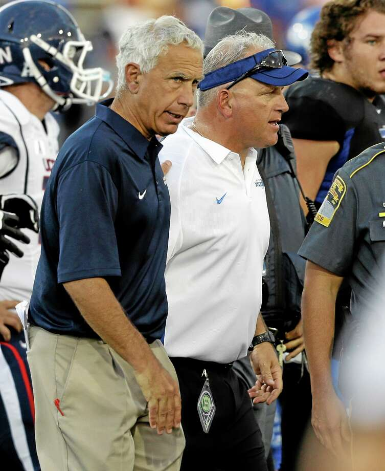 UConn head coach Paul Pasqualoni, left, walks off the field after Saturday's loss to Buffalo. Photo: Mike Groll — The Associated Press  / AP