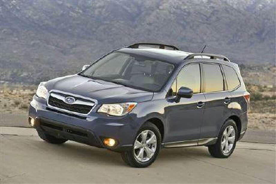 This photo provided by Subaru shows the 2014 Subaru Forester. The Subaru Forester, well known as a durable and eminently functional compact sport utility vehicle, adds more power, more room, more safety features and a retuned suspension for 2014. The new, fourth-generation Forester also has higher fuel economy ratings than its predecessor, 24 miles per gallon in city driving and 32 mpg on the highway with base, 170-horsepower, four-cylinder engine and fuel-efficient continuously variable transmission (CVT). (AP Photo/Subaru) Photo: AP / Subaru