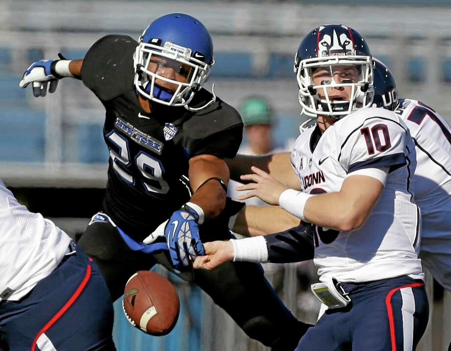 Buffalo defensive back Adam Redden forces a fumble by UConn quarterback Chandler Whitmer during the first half Saturday. Photo: Mike Groll — The Associated Press  / AP