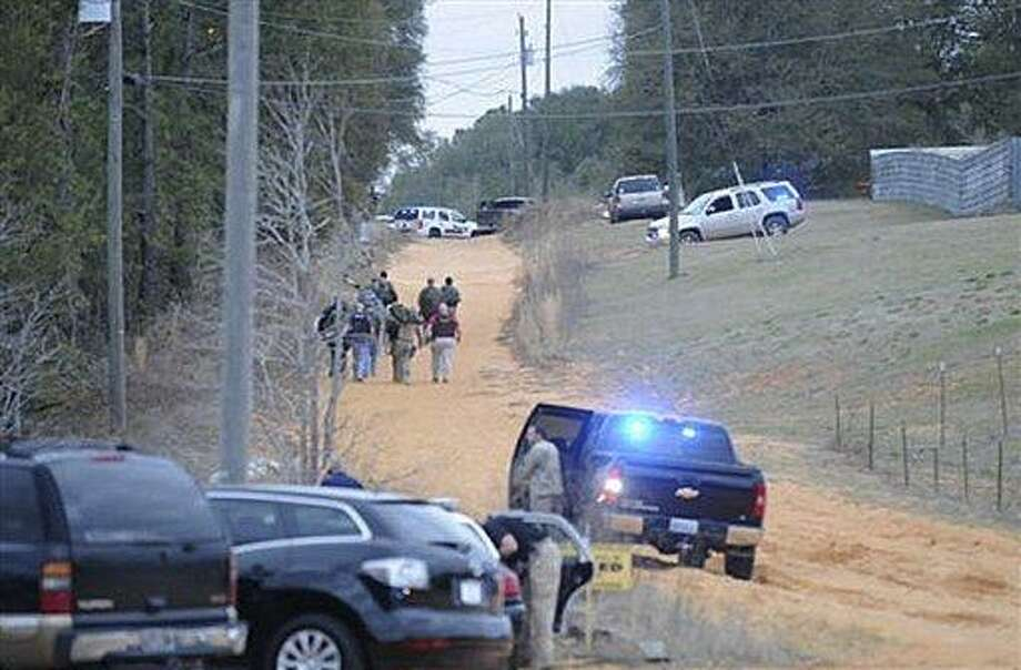 In this Tuesday, Jan 29, 2013 photo, law enforcement officers walk up the road toward a home where a school bus shooting suspect was hiding inside a bunker late Tuesday. Police, SWAT teams and negotiators were at a rural property where a man was believed to be holed up in a homemade bunker Wednesday, HAN 30, 2013 after fatally shooting the driver of a school bus and fleeing with a 6-year-old child passenger, authorities said. The man boarded the stopped school bus in the town of Midland City on Tuesday afternoon and shot the driver when he refused to let the child off the bus. The bus driver died. (AP Photo/The Dothan Eagle, Danny Tindell) Photo: AP / Dothan Eagle