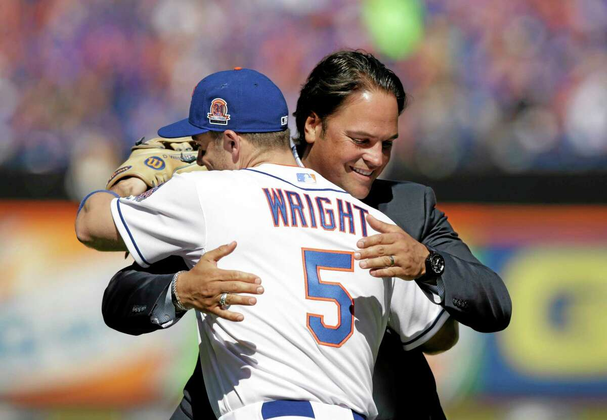 Former Mets catcher Mike Piazza embraces third baseman David Wright (5) after throwing out the ceremonial first pitch Sunday.