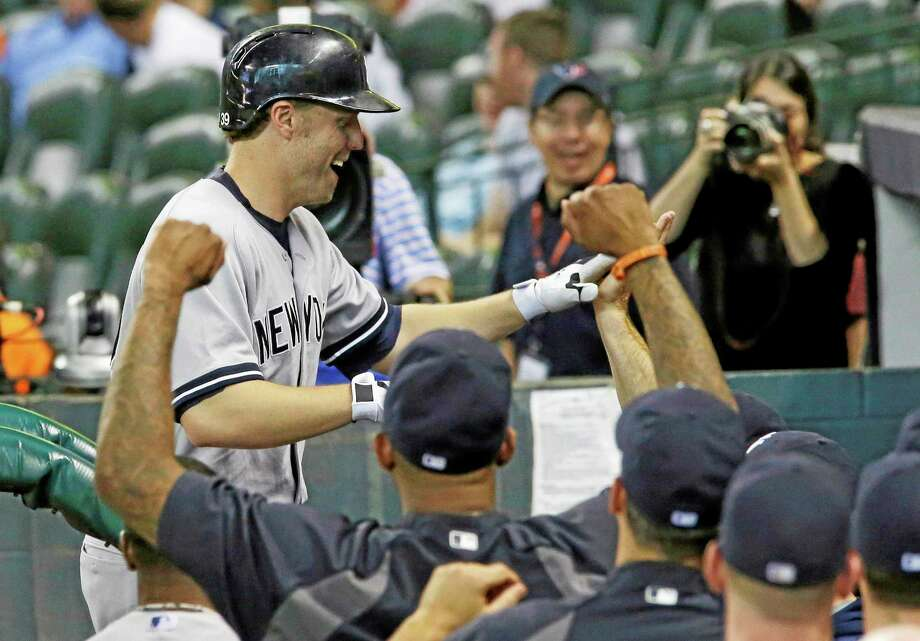 Mark Reynolds is greeted by teammates after his solo home run in the 14th inning against the Houston Astros Sunday. Photo: Richard Carson — The Associated Press  / FR171014 AP