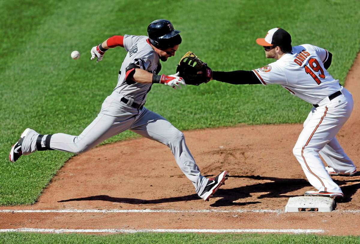 Jacoby Ellsbury, left, runs toward first base as Orioles first baseman Chris Davis reaches for a throw in the fourth inning Sunday.