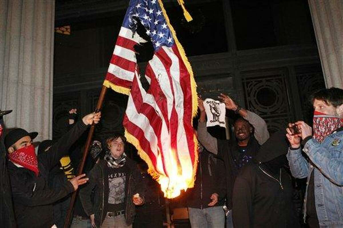 Occupy Oakland protestors burn an American flag found inside Oakland City Hall during an Occupy Oakland protest on the steps of City Hall Saturday in Oakland, Calif. Associated Press