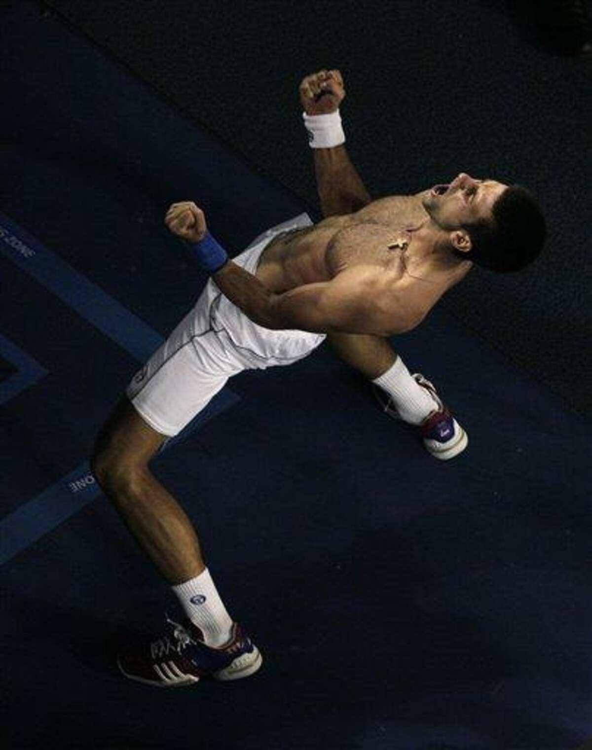 Novak Djokovic of Serbia celebrates after defeating Rafael Nadal of Spain during the men's singles final at the Australian Open tennis championship, in Melbourne, Australia, Monday, Jan. 30, 2012. Associated Press