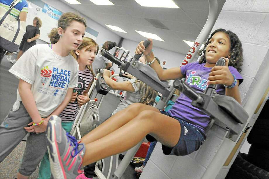 Keigwin student Amaya White, 10, uses the all-purpose machine in the middle school's weight room to do leg raises last Tuesday at CrossFit Club, an after-school fitness program run by Middletown High School gym teacher, Mark Fong. Nicole Nenniger, 11, and Rachel Markovics, 10, wait for their turn. The CrossFit Club meets every Tuesday and Thursday. Catherine Avalone - The Middletown Press Photo: Journal Register Co. / TheMiddletownPress