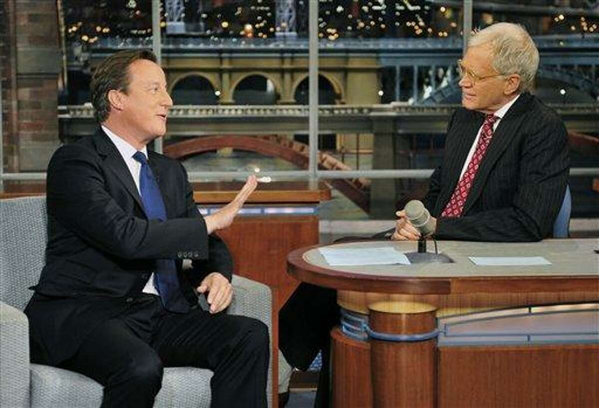 In this photo provided by CBS, British Prime Minister David Cameron, left, talks with host David Letterman on the set of the