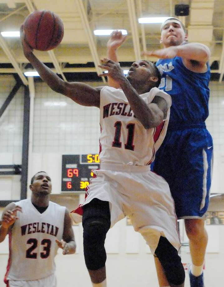 Catherine Avalone/The Middletown PressWesleyan senior guard Shasha Brown (Harlem N.Y.) goes up for two against U.S. Merchant Marine Academy freshman forward Andrew Williams Monday night in Middletown. Wesleyan junior forward Glen Thomas (Washington D.C.) watches the play. The Cardinals defeated U.S.M.M.A.