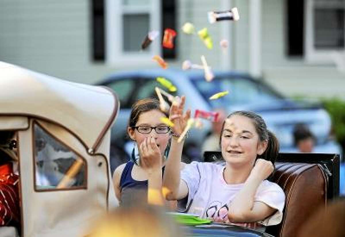 Steve McLauglin/Special to the Press Michelle Corriveau, right, and Amber Strugoff, both of Cromwell, throw candy to childern along the parade route.