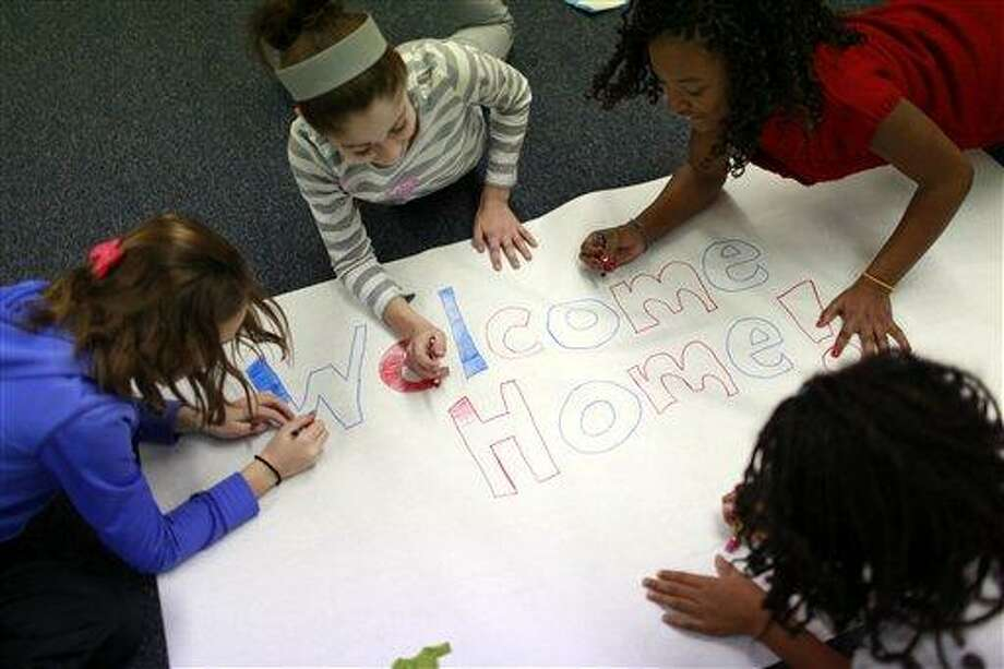 "Ross Elementary fifth-grade students, clockwise from left, Juilanna Bell, Mollie Weinberg, Courtney Turner and Mckenzie Thompson, work to create a hand-made sign Wednesdayin Creve Coeur, Mo., to take to the St. Louis ""Welcome Home the Heroes from Iraq Day"" today. Associated Press Photo: AP / AP"