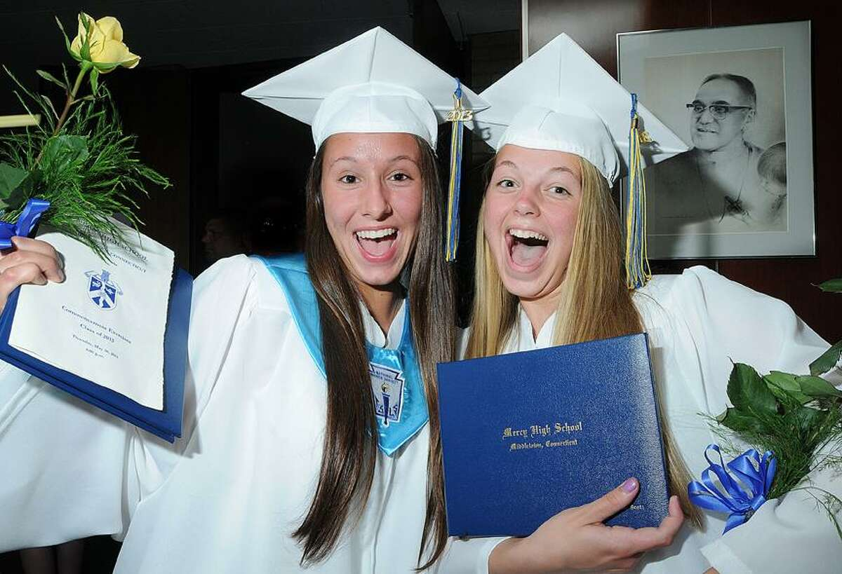 Catherine Avalone/The Middletown PressAlexandra Piel, left and Victoria Scott, at right members of Mercy High School's class of 2013 celebrate following the recessional commencement Thursday evening in the school foyer.