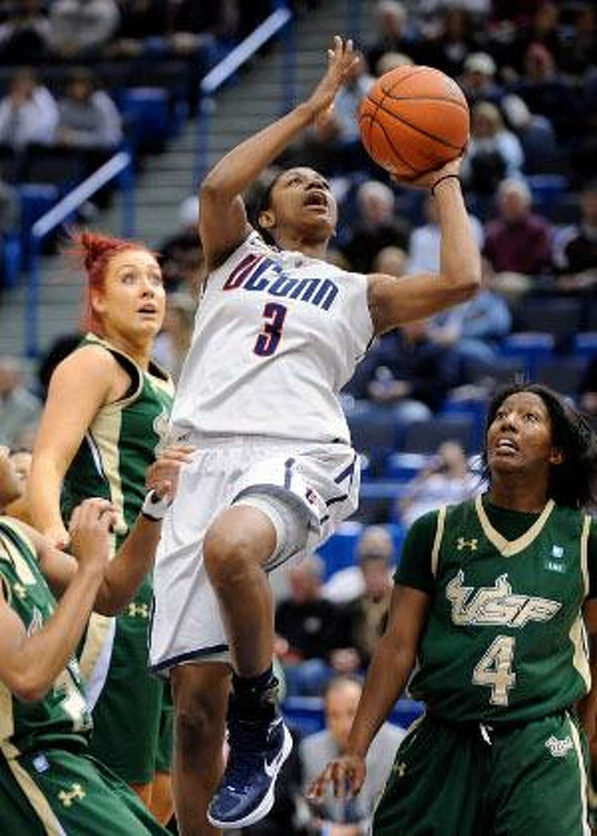 ASSOCIATED PRESS Connecticut's Tiffany Hayes, center, drives past South Florida's Caitlin Rowe, left, and Tiffany Conner (4) during the first half of Saturday's game in Hartford.