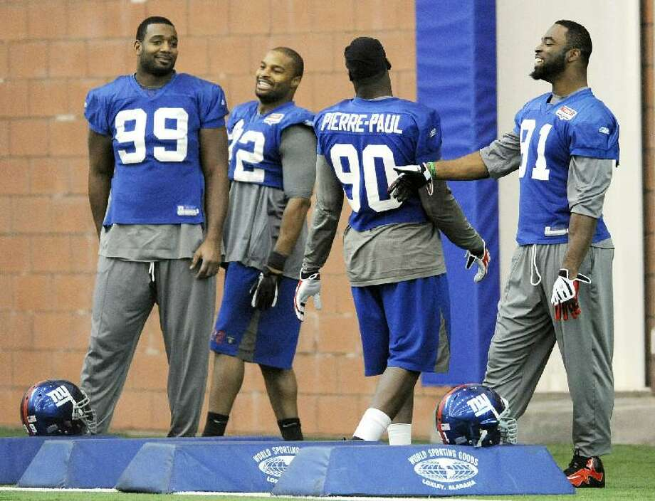 ASSOCIATED PRESS In this Jan. 19 photo, New York Giants defensive linemen Chris Canty (99), Osi Umenyiora (72), Jason Pierre-Paul (90) and Justin Tuck share a laugh during practice in East Rutherford, N.J. The Giants play the New England Patriots in Super Bowl XLVI on Feb. 5 in Indianapolis.