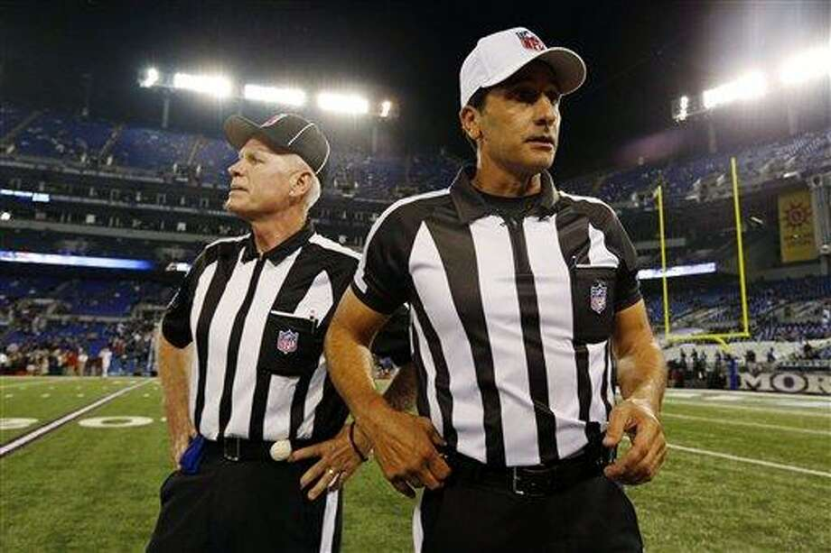 Referee Gene Steratore, right, and back judge Bob Waggoner, left, look around the field before an NFL football game between the Baltimore Ravens and Cleveland Browns in Baltimore, Thursday, Sept. 27, 2012. (AP Photo/Patrick Semansky) Photo: ASSOCIATED PRESS / AP2012
