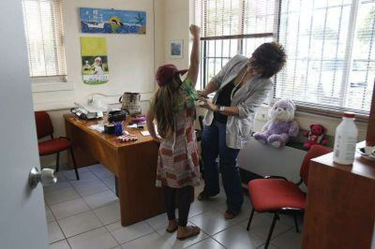 A pediatrician examines a girl inside a social medical centre in the Helliniko suburb of Athens May 24, 2012.