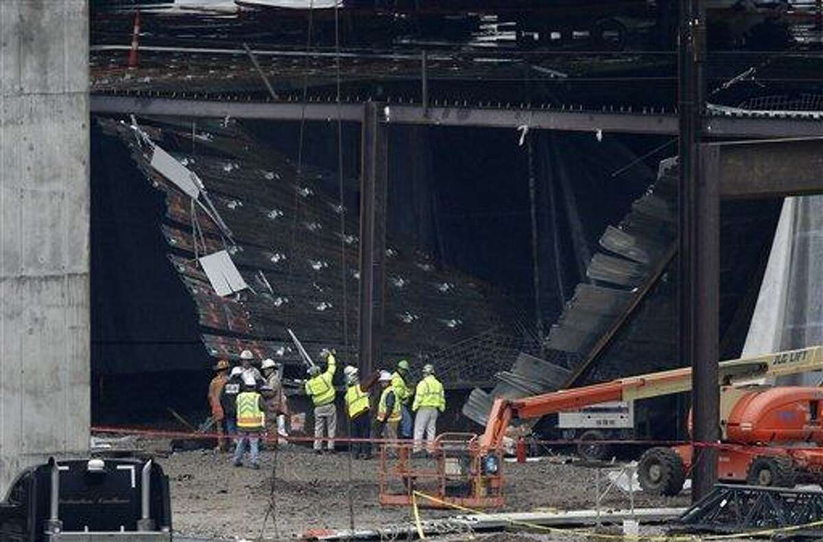 Officials inspect the scene of a collapsed floor at the construction site of the new casino being built in downtown Cincinnati Friday. A section of floor collapsed, sending workers tumbling down with it and causing minor injuries for at least 11 people, authorities said. Associated Press