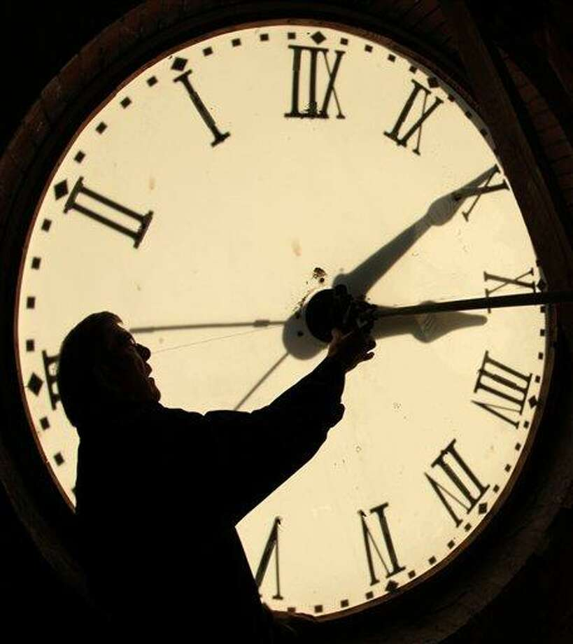FILE - Custodian Ray Keen checks the time on a clock face after changing the time on the 97-year-old clock atop the Clay County Courthouse, in this Nov. 6, 2010 file photo taken in Clay Center, Kan. Most Americans will be able to get an extra hour of sleep Sunday Nov. 4, 2012 thanks to the annual shift back to standard time. Officially, the change occurs at 2 a.m. Sunday, but most people will set their clocks back before hitting the sack Saturday night. (AP Photo/Charlie Riedel, File) Photo: AP / AP