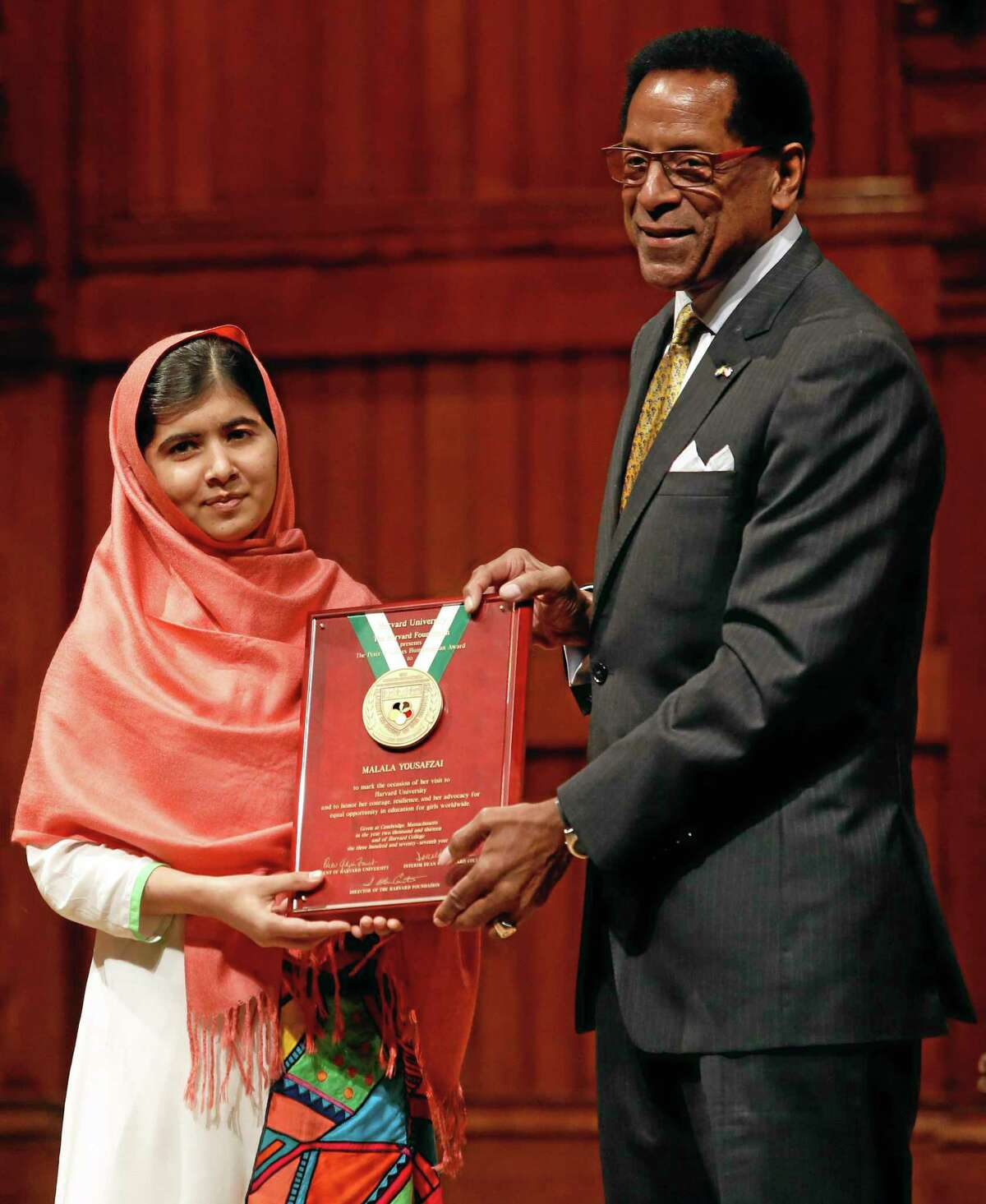Malala Yousafzai, left, is presented with the 2013 Peter J. Gomes Humanitarian Award by Director of the Harvard Foundation and Professor of Neurology at Harvard Medical School Dr. S. Allen Counter, right, at Harvard University Friday, Sept. 27, 2013, on the school's campus in Cambridge, Mass. The Pakistani teenager, an advocate for education for girls, survived a Taliban assassination attempt last year on her way home from school. (AP Photo/Jessica Rinaldi)