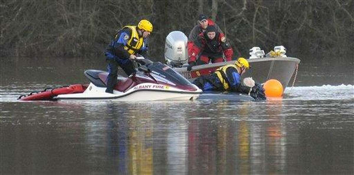 Divers from the Albany Fire Department pull an elderly man from a submerged car in the area of Bryant Drive near Albany, Ore., Thursday. The man, who drove past two