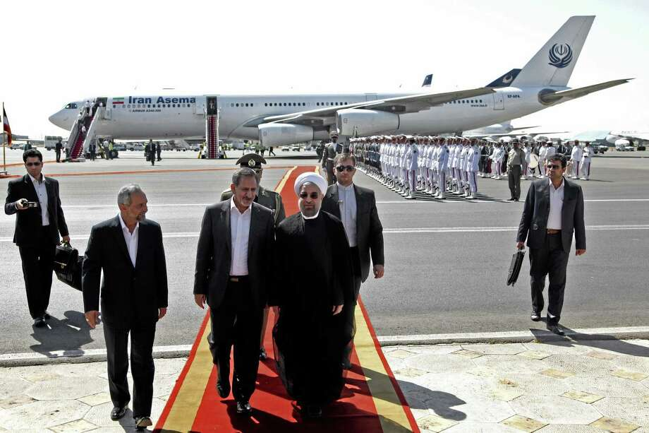 Iranian President Hassan Rouhani, center, walks with and Vice President Eshagh Jahangiri, center left, at Mehrabad airport in Tehran, Iran, Saturday. Iranians from across the political spectrum hailed Saturday the historic phone conversation between President Barack Obama and his Iranian counterpart Hassan Rouhani. Photo: Ebrahim Noroozi — The Associated Press  / AP
