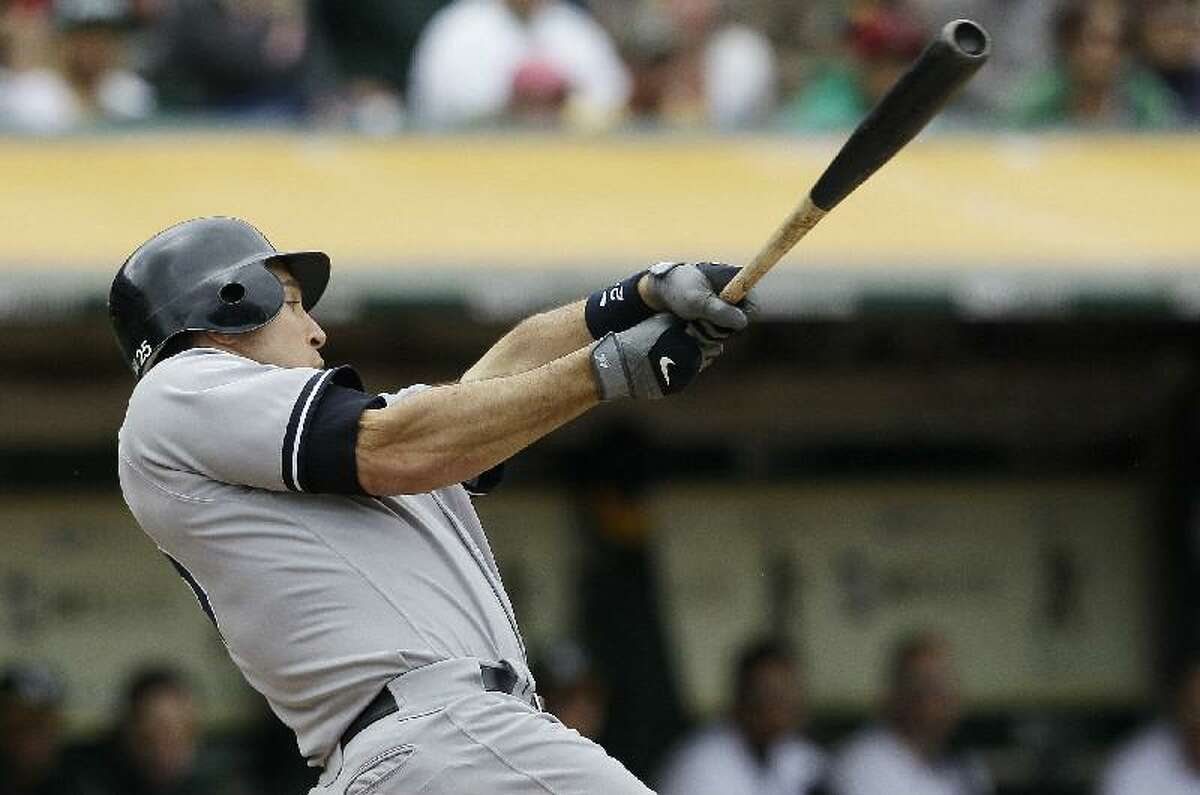 ASSOCIATED PRESS New York Yankees first baseman Mark Teixeira hits a two-run home run off Oakland Athletics pitcher Graham Godfrey during the eighth inning of Saturday's game in Oakland, Calif. Teixeira homered twice in a 9-2 win.