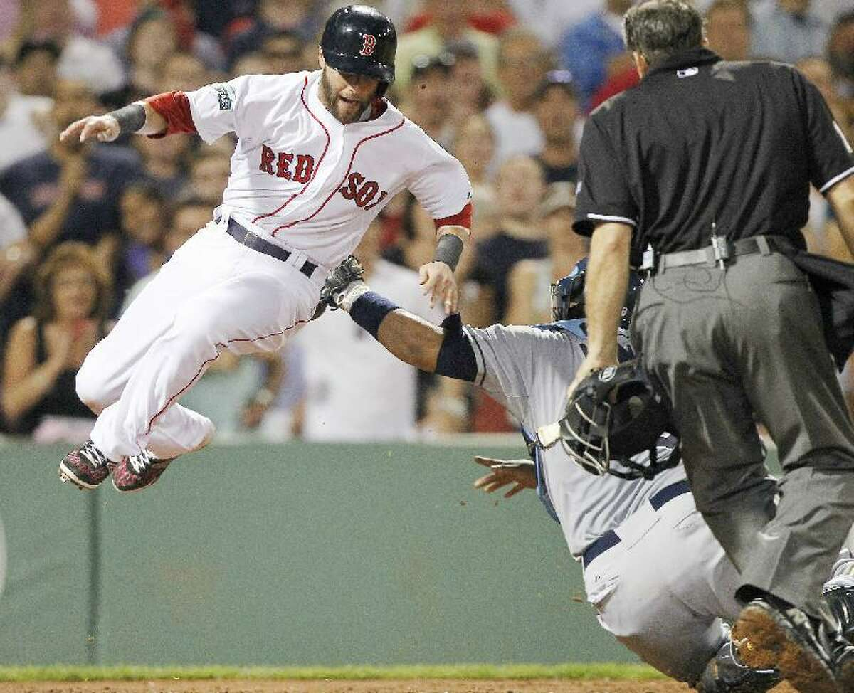 ASSOCIATED PRESS Tampa Bay Rays catcher Jose Molina, right back, tags Boston Red Sox shortstop Dustin Pedroia, left, at home plate in the sixth inning of Saturday's game at Fenway Park in Boston.