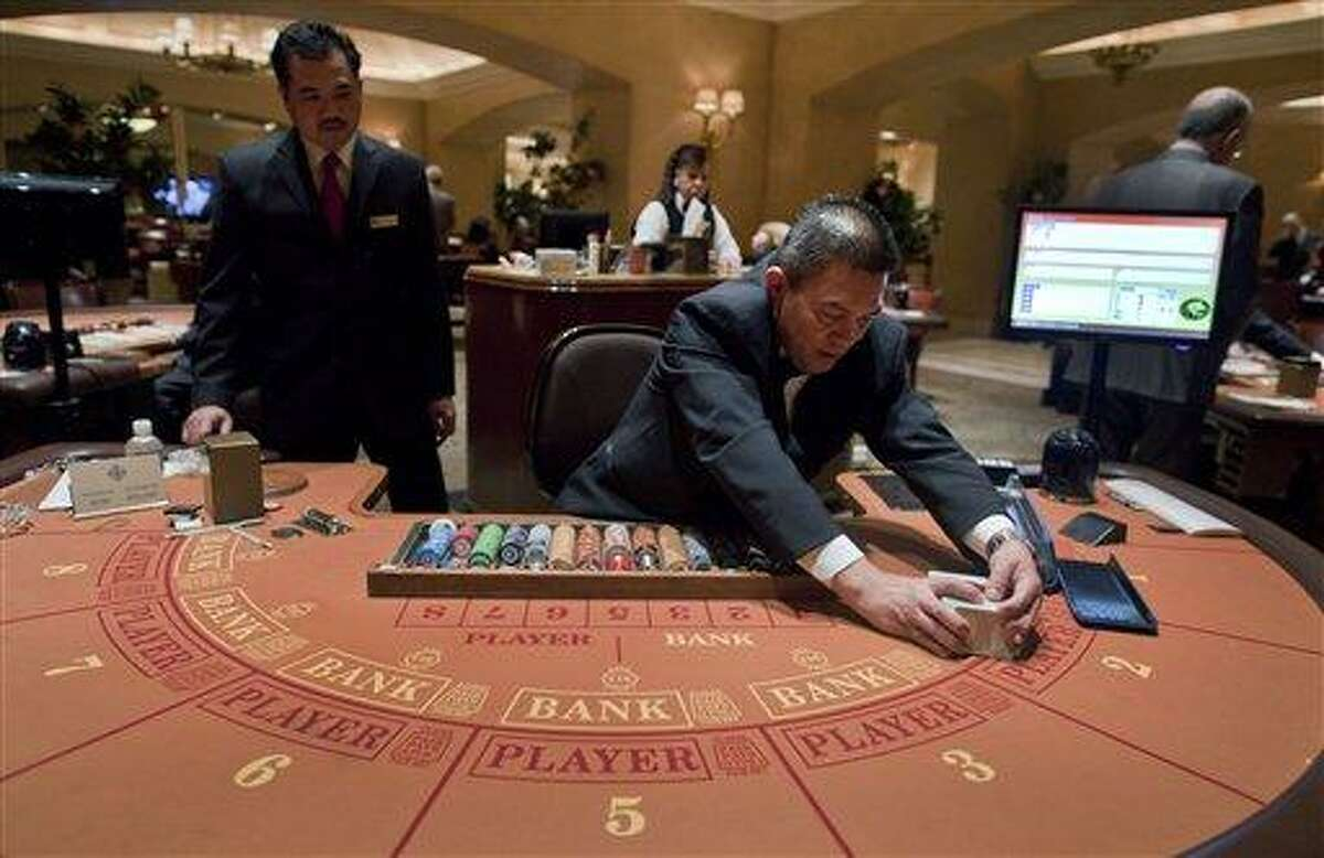 Baccarat dealer Ramiro Nepomuceno, right, shuffles cards as floor supervisor Sam Insyxiengmay looks on while preparing a table for play at the MGM Hotel and Casino Wednesday in Las Vegas. There are generally more Asian gamblers in Vegas because of the Chinese New Year, and it means increased traffic at high limit baccarat tables. Though not widely known, baccarat is actually the most profitable table game for casinos, which try to court Asian gamblers who tie luck and good fortune to the start of the Lunar Year. Associated Press