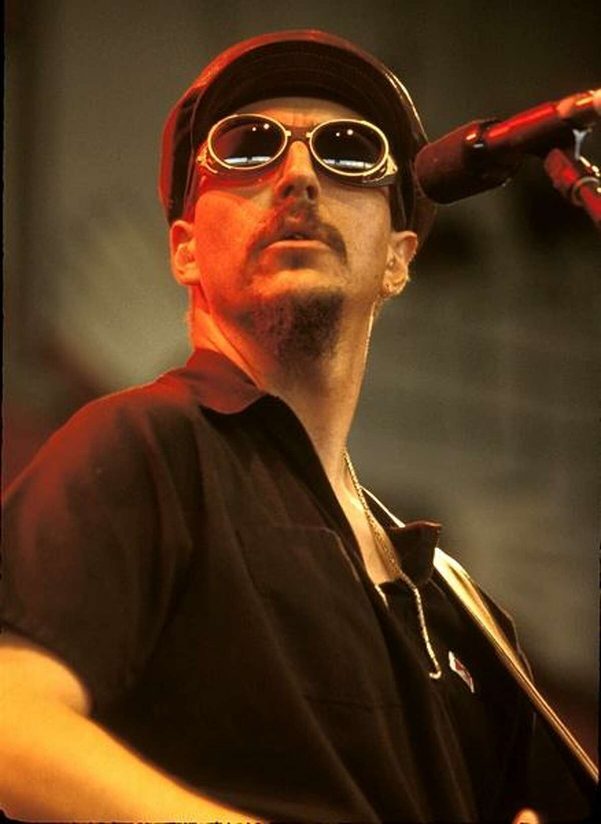 Singer and bassist Les Claypool of the rock band Primus is shown performing on stage during a