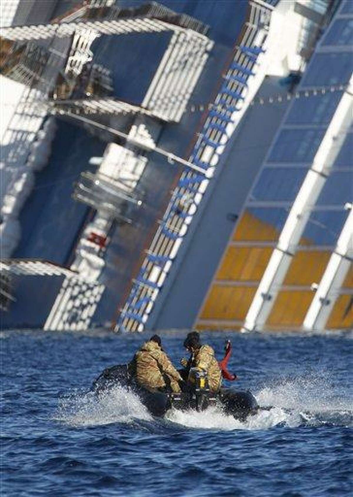 Italian Navy scuba divers head toward the grounded Costa Concordia off the Tuscan island of Giglio, Italy. The search continues for missing passengers and crew. Associated Press