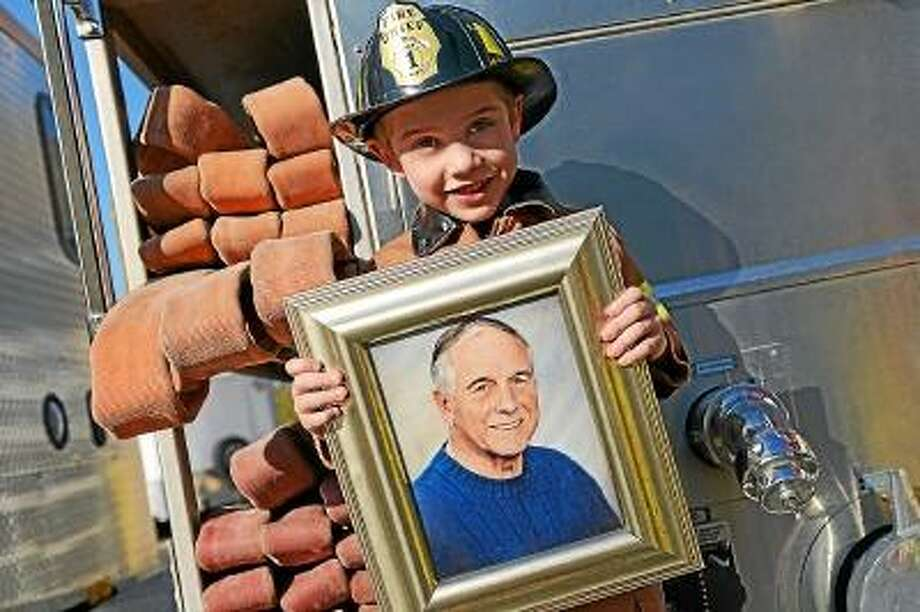 """Olivia Drake/Special to the Press Jamie and Teresa's boy Martin holds a picture of his great uncle Robert """"Bobby"""" Kuchyt, who died in 2009."""