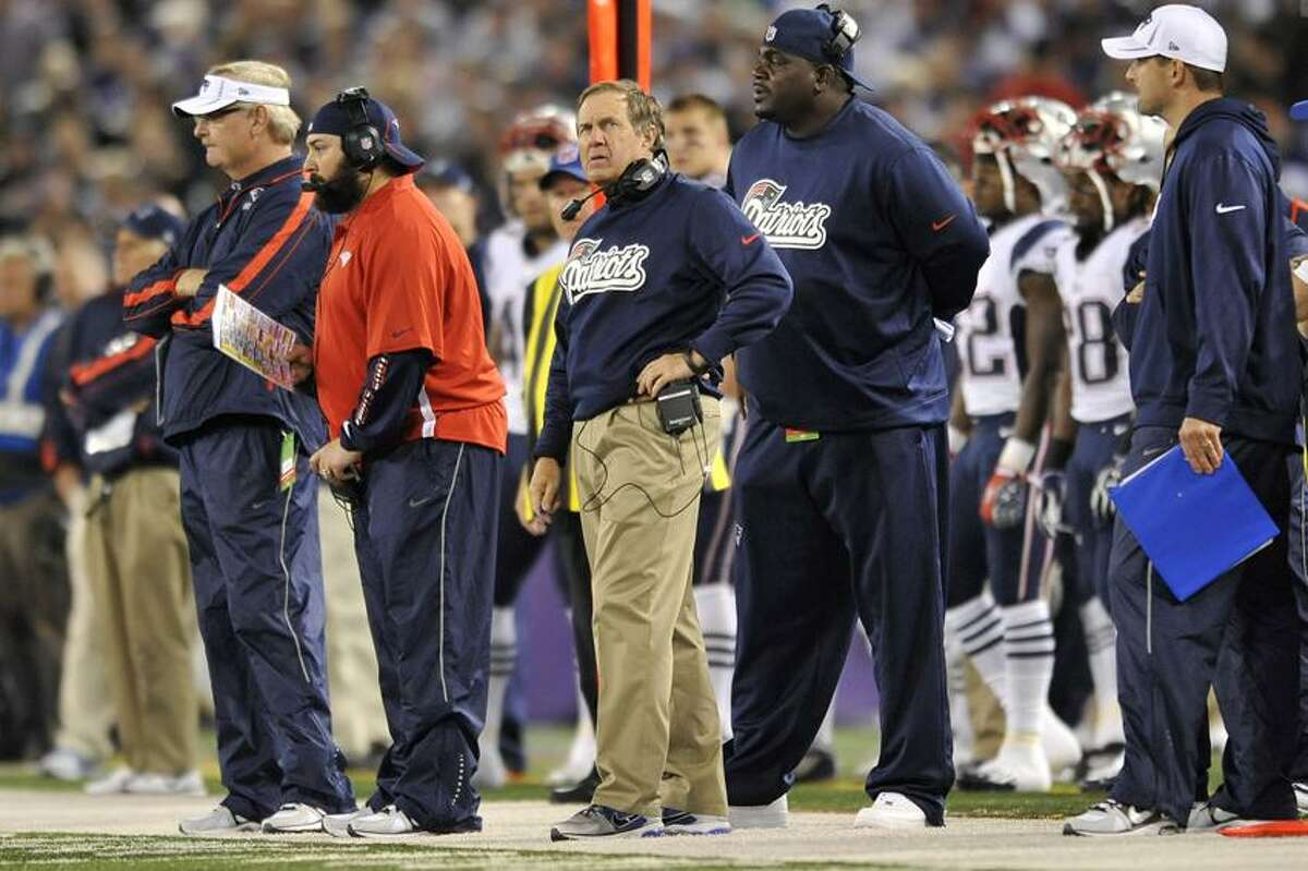 New England Patriots head coach Bill Belichick, center, looks on in the first half of an NFL football game against the Baltimore Ravens in Baltimore, Sunday, Sept. 23, 2012. (AP Photo/Gail Burton)