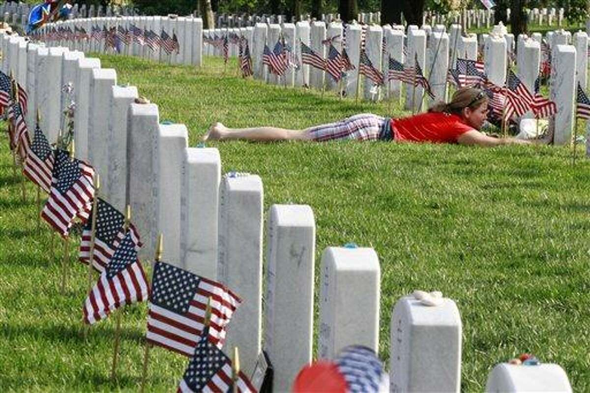 Air Force Major Terry Dutcher, of Hill Air Force Base, Utah, touches the headstone of her son, Army Corporal Michael Avery Pursel, who died serving in Iraq in 2007 at age 19, surrounded by flags placed by soldiers at each grave for the annual