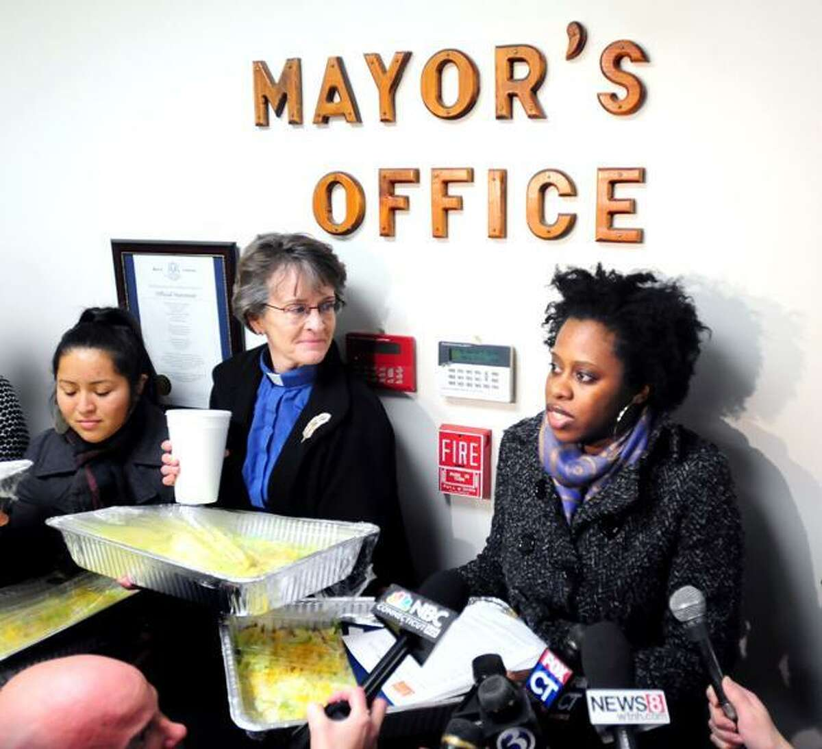 Mirtala Sanchez of Mecha De Yale (left), Kathleen McTigue (center), senior minister, Unitarian Society of New Haven, listen to Latrina Kelly (right), interim executive director of the Junta for Progressive Action, make a statement during a delivery of nearly 500 tacos to the office of Mayor Joseph Maturo, Jr., at East Haven Town Hall on 1/26/2012.Photo by Arnold Gold/New Haven Register AG0436E