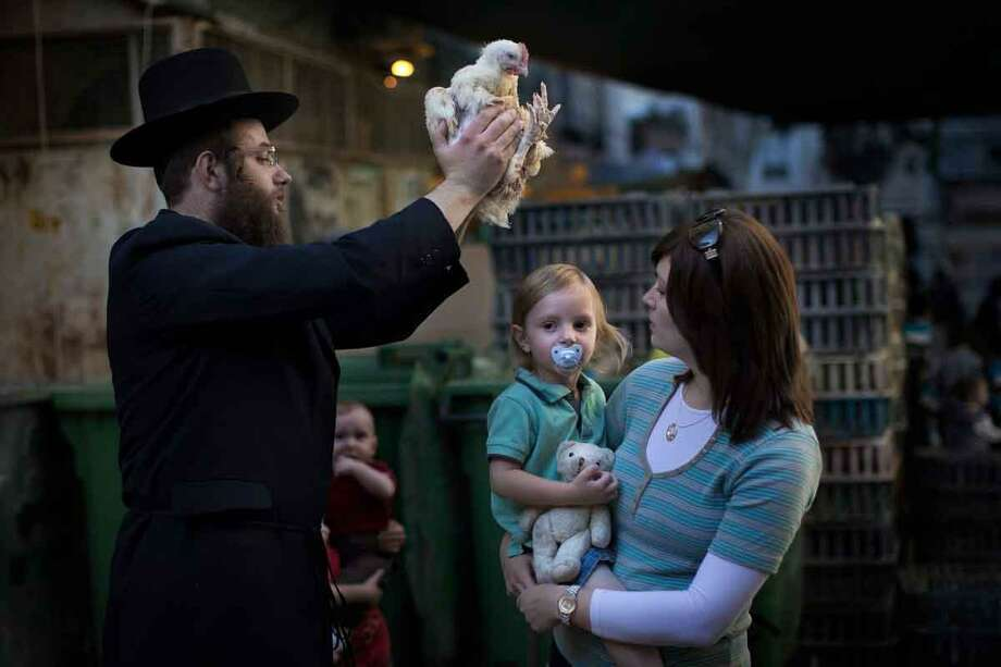 An ultra-Orthodox Jewish man swings a chicken over this son's head, as part of the Kaparot ritual, in which it is believed that one transfers one's sins from the past year into the chicken, in Jerusalem's religious Mea Shearim neighborhood, Sunday, Sept. 23, 2012. The ceremony is held before the Jewish holiday of Yom Kippur, the Day of Atonement. (AP Photo/Bernat Armangue) Photo: ASSOCIATED PRESS / AP2012