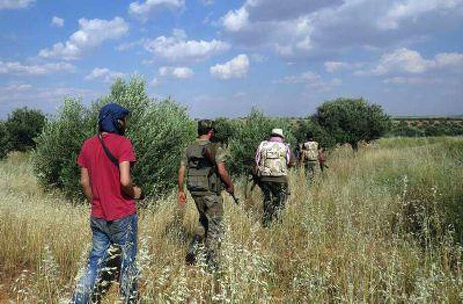 Ill-equipped Syrian rebels walk through a field in Idlib province, northern Syria. Photo: AP / Edlib News Network ENN