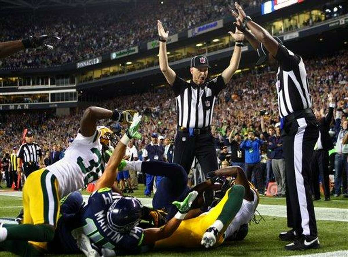 Officials signal after Seattle Seahawks wide receiver Golden Tate pulled in a last-second pass for a touchdown from quarterback Russell Wilson to defeat the Green Bay Packers 14-12 in an NFL football game, Monday, Sept. 24, 2012, in Seattle. The touchdown call stood after review. (AP Photo/seattlepi.com, Joshua Trujillo)