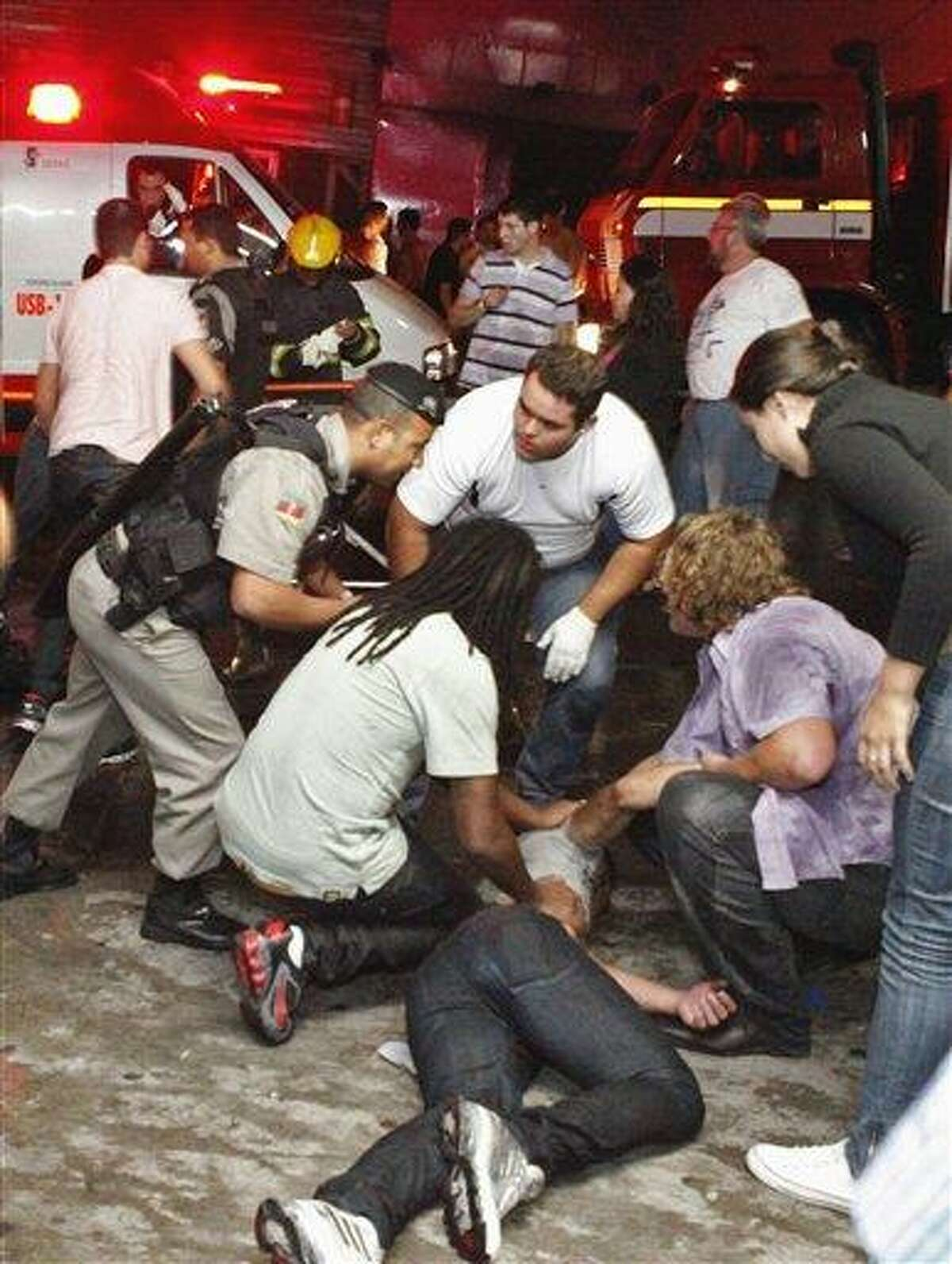 People help an injured man, victim of a fire in a club in Santa Maria city, Rio Grande do Sul state, Brazil, Sunday. According to police more than 200 died in the devastating nightclub fire in southern Brazil. Officials say the fire broke out at the Kiss club in the city of Santa Maria while a band was performing. At least 200 people were also injured. (AP Photo/Agencia RBS)