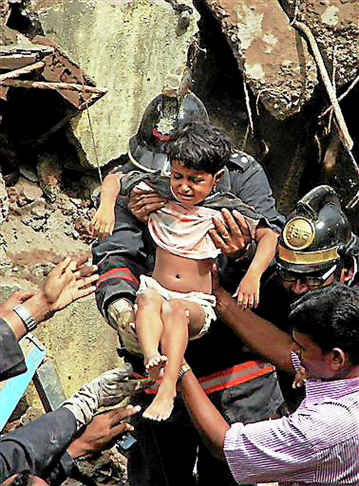 Indian Fire officials rescue a girl from the debris of a collapsed building in Mumbai, India, Friday, Sept. 27, 2013. The multi-story residential building collapsed in India's financial capital of Mumbai early Friday, killing at least three people and sending rescuers racing to reach dozens of people feared trapped in the rubble. (AP Photo)