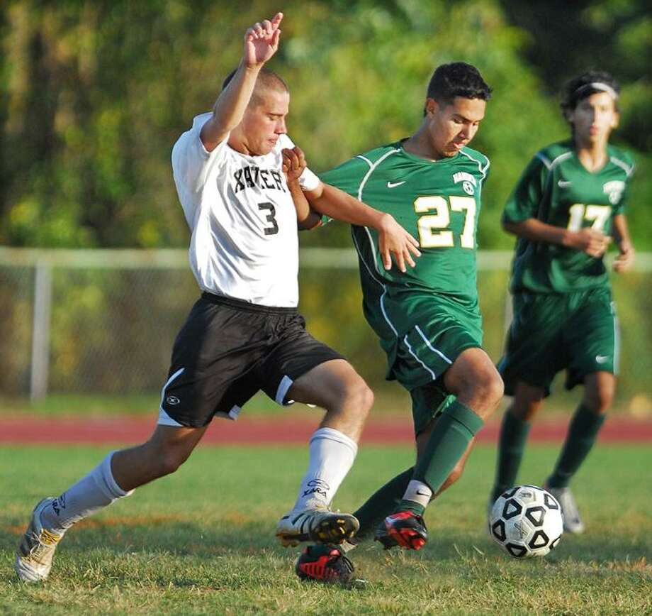 @CAvaloneMP  9.25.12   Xavier's Anthony Chiozzi attempts to avoid a collision with Hamden's Jason Durnin during a 2-0 win for the Falcons at home in Middletown Tuesday afternoon.