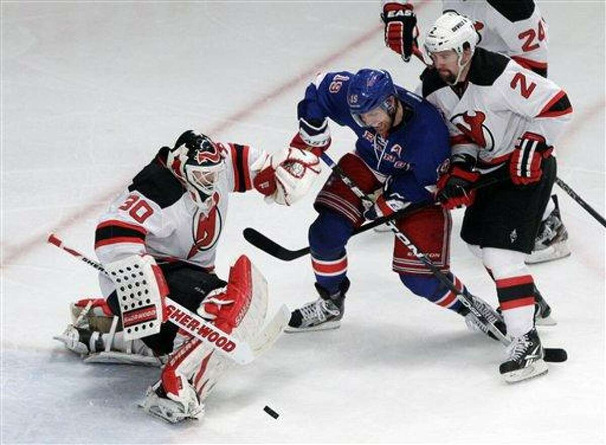 New Jersey Devils Martin Brodeur, left, stops the puck near New York Rangers' Brad Richards and Devils' Marek Zidlicky, of the Czech Republic, during the second period of Game 5 of an NHL hockey Stanley Cup Eastern Conference final playoff series, Wednesday, May 23, 2012, in New York. The Devils won 5-3. (AP Photo/Frank Franklin II)