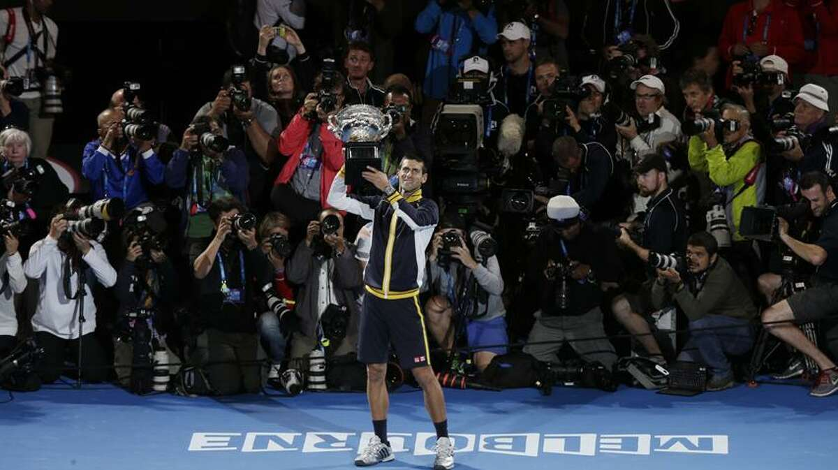 Serbia's Novak Djokovic holds his trophy after defeating Britain's Andy Murray in the men's final at the Australian Open tennis championship in Melbourne, Australia, Monday, Jan. 28, 2013. (AP Photo/Andy Wong)