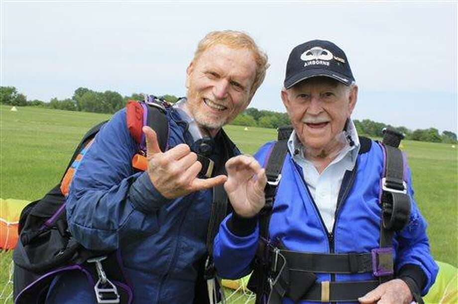 This photo provided by Skydive Warren County, Inc. shows Clarence Turner, an 87-year-old World War II veteran who parachuted into Japan, right, celebrating with instructor Jeff McGinnis after they parachuted in tandem at the Red Stewart Airfield near Waynesville, Ohio, Saturday, May 25, 2013. Turner made the jump to generate attention for the plight of his 10-month-old great-grandson, Julian Couch, who suffers from a lung disease. (AP Photo/Skydive Warren County, Inc., Elod Otbos) Photo: ASSOCIATED PRESS / AP2013