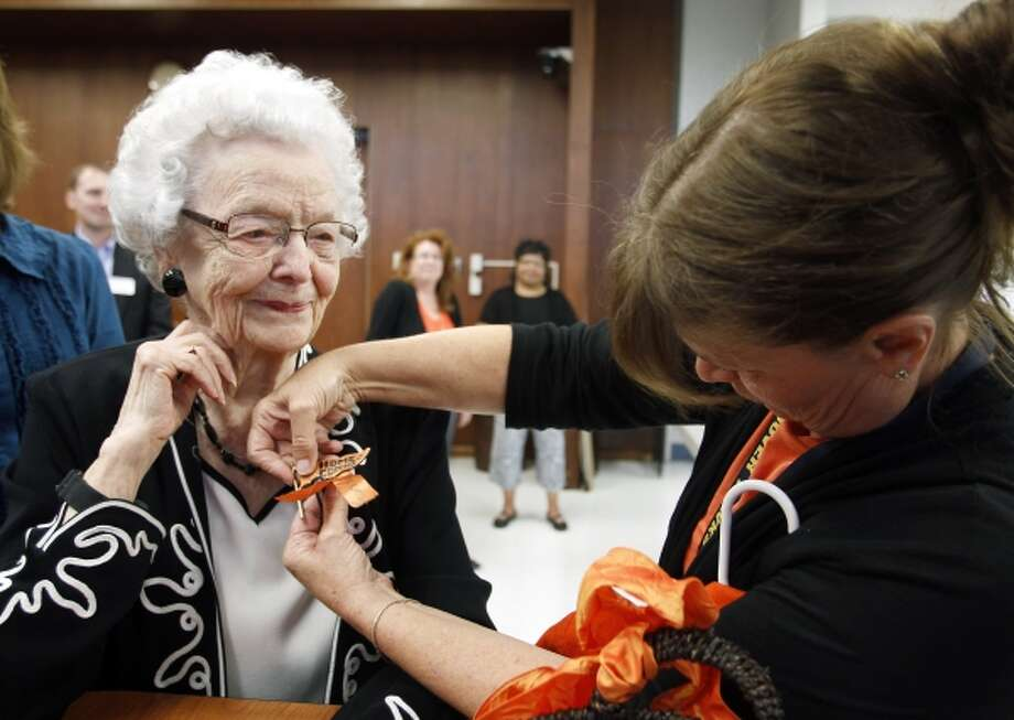 In this Sept. 23, 2013, Audrey Crabtree, 99, left, smiles as Sarah Dierks pins a 1972 East High homecoming pin onto her jacket during an during an education board meeting in Waterloo, Iowa, where she received an honorary diploma. Crabtree dropped out of a Waterloo high school in 1932 due to an injury and to care for her grandmother. She went on to run her own business for nearly three decades. (AP Photo/Waterloo Courier, Tiffany Rushing) Photo: AP / THE WATERLOO COURIER