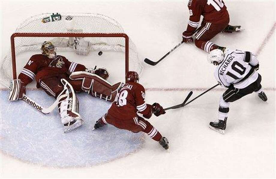 Los Angeles Kings' Mike Richards (10) scores against Phoenix Coyotes' Mike Smith, far left, as Coyotes' Lauri Korpikoski (28), of Finland, defends in the second period during Game 5 of the NHL hockey Stanley Cup Western Conference finals Tuesday, May 22, 2012, in Glendale, Ariz.  The Kings defeated the Coyotes 4-3, and advance to the Stanley Cup Finals.(AP Photo/Ross D. Franklin) Photo: AP / AP