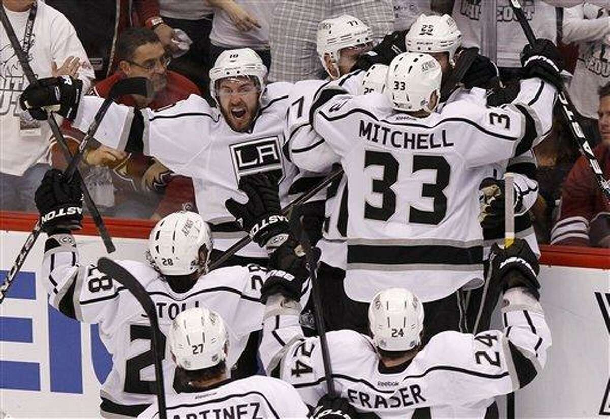 Los Angeles Kings' Mike Richards (10) shouts in celebration as teammates Jeff Carter (77), Willie Mitchell (33), Jarret Stoll (28), Alec Martinez (27), and Colin Fraser (24) converge on Dustin Penner (25), who scored the game-winner against the Phoenix Coyotes in overtime during Game 5 of the NHL hockey Stanley Cup Western Conference finals Tuesday, May 22, 2012, in Glendale, Ariz. The Kings defeated the Coyotes 4-3, and advance to the Stanley Cup Finals.(AP Photo/Ross D. Franklin)