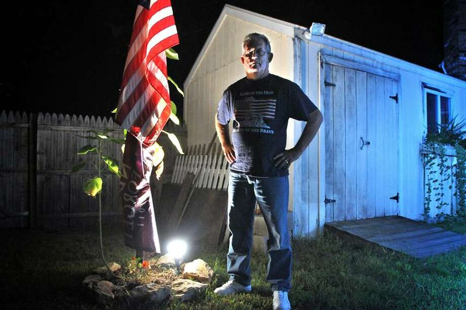 Thomas Hackley stands next to a lit flag in his backyard. Police ticketed him and have told him to change the lighting after a complaint from a neighbor. Photo Peter Casolino/New Haven Register