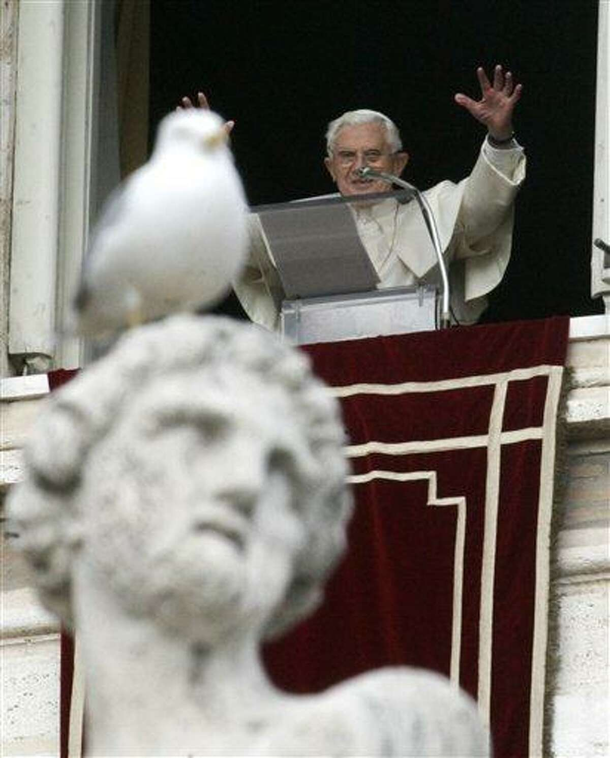 File photo from December, 2011, shows Pope Benedict XVI as he greets faithful during the Angelus prayer from his studio overlooking St. Peter's square, Vatican. Associated Press