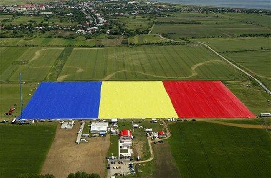 An aerial picture shows a huge Romanian flag on the Clinceni Airfield, south of Bucharest, Romania, Monday, May 27, 2013. Romania entered the Guinness Book of records after it unveiled the largest flag ever made. It took about 200 people several hours Monday to unfurl a five-ton flag of Romania which organizers said measured 349.4 meters by 226.9 meters, about three times the size of a football pitch.(AP Photo/Bogdan Cristel, Pool) Photo: AP / POOL REUTERS