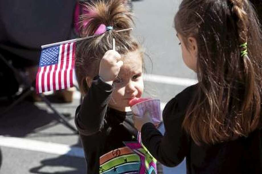 Sandy Aldieri/Special to the Press Gracie Doolittle feeds her little sister, Maddie, some lemon ice as they wait for Middletown's Memorial Day Parade to begin.