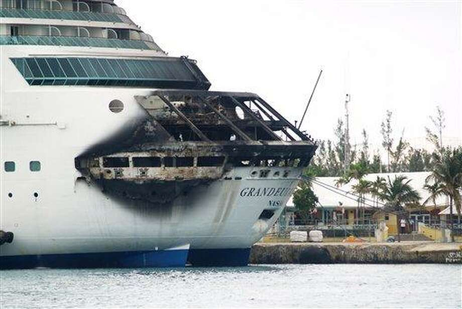 The fire-damaged exterior of Royal Caribbean's Grandeur of the Seas cruise ship is seen while docked in Freeport, Grand Bahama island, Monday, May 27, 2013. Royal Caribbean said the fire occurred early Monday while on route from Baltimore to the Bahamas on the mooring area of deck 3 and was quickly extinguished. All 2,224 guests and 796 crew were safe and accounted for. (AP Photo/The Freeport News, Jenneva Russell) Photo: AP / The Freeport News